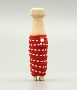 Dekorativt band i rött med vit detalj trädd på en träspole