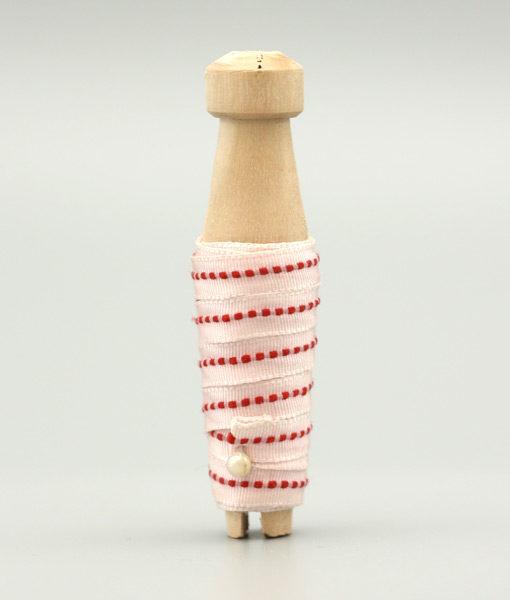 Tetilband i vitt med röd detalj trädd på en träspole