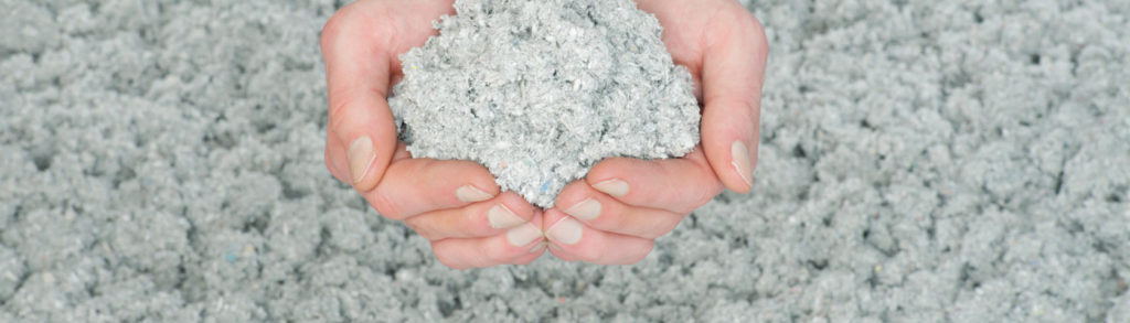 händer som håller i cellulosaisolering lösull ett miljövänligt byggmaterial för byggnadsvård