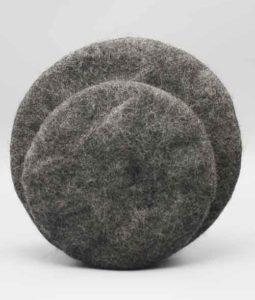 Grytunderlägg av mörkgrå tovad ull med kork och läder